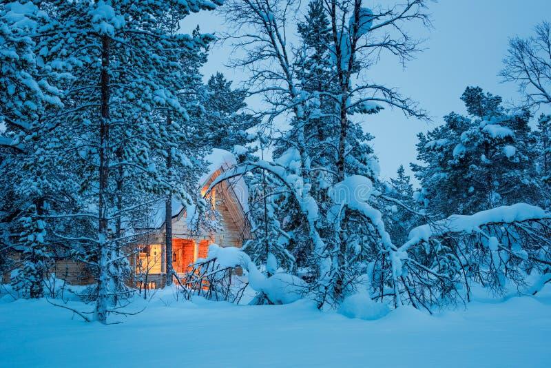 Noche de hadas del invierno - cabaña de madera en bosque nevoso imagen de archivo