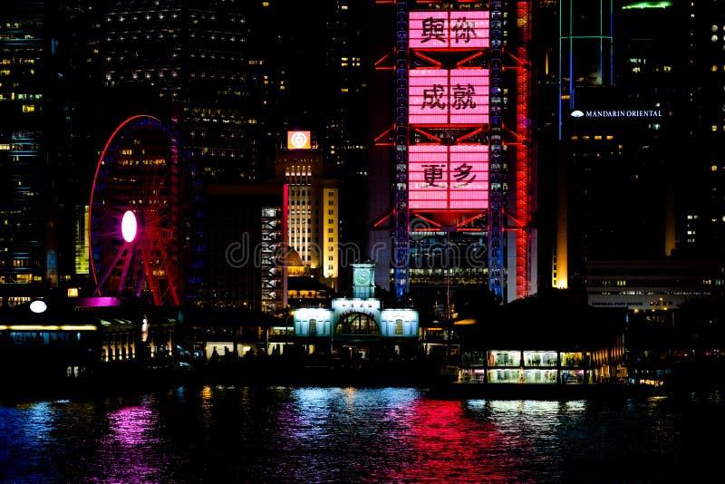 Noche de Hong-Kong Embarcadero central, noria, publicidad colorida, ideogramas chinos, reflexiones hermosas fotografía de archivo
