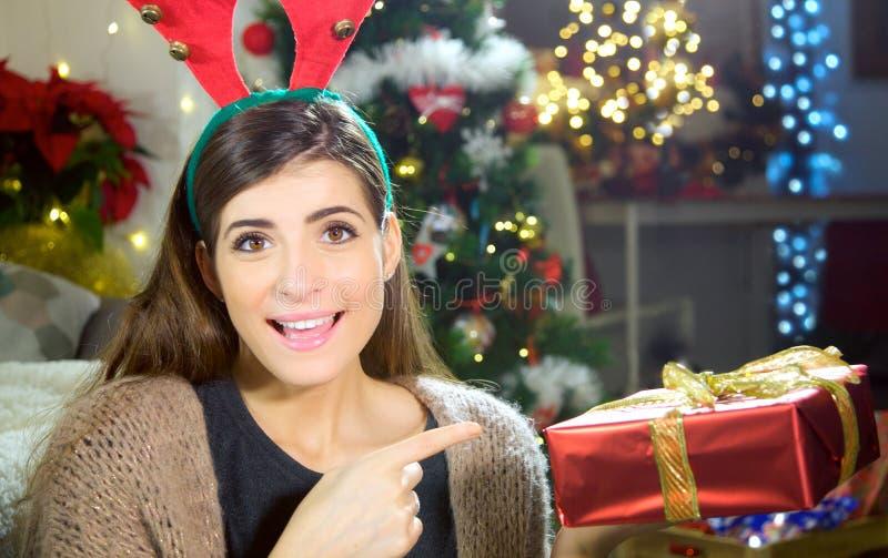 Noche de la Navidad linda de la mujer joven en casa que muestra el regalo de la caja feliz foto de archivo