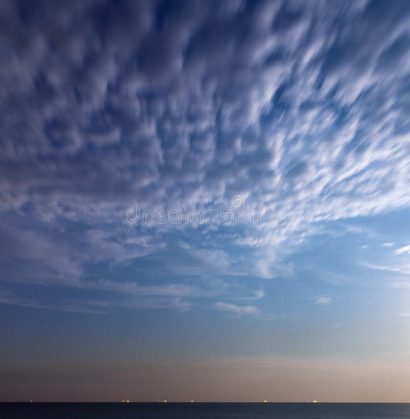 Noche de verano hermosa en el mar con el cielo azul y las nubes fotografía de archivo