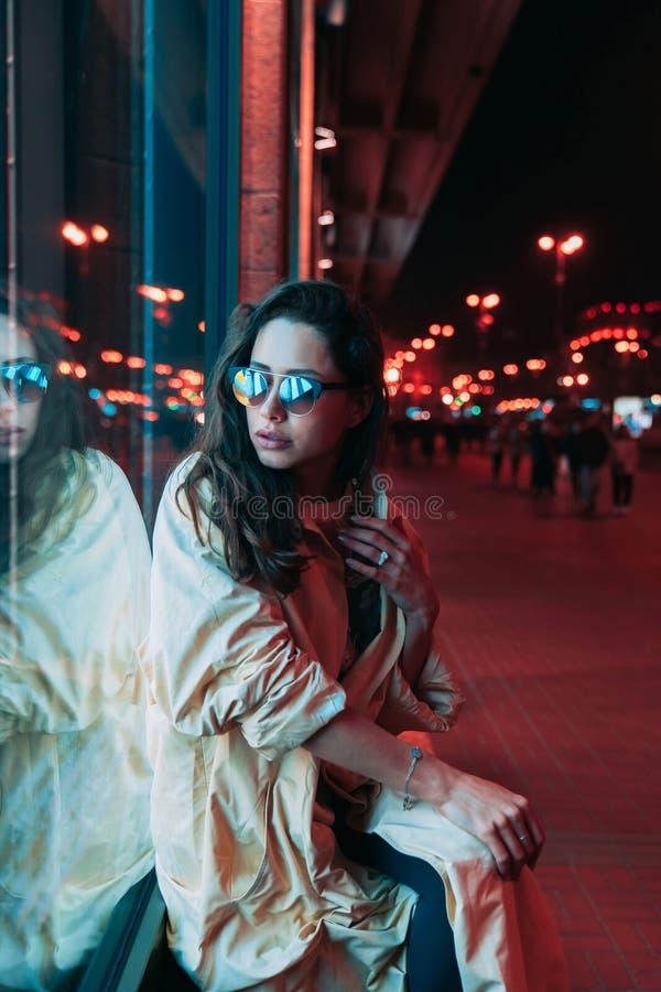 Noche en la ciudad, mujer hermosa entre luces rojas fotografía de archivo