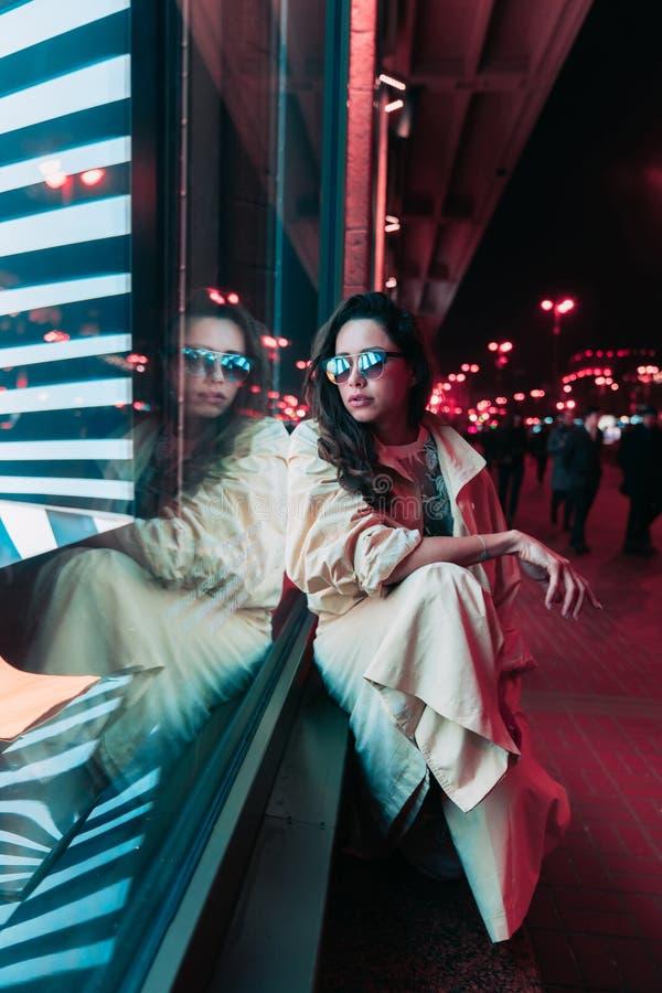 Noche en la ciudad, mujer hermosa entre luces rojas imagen de archivo