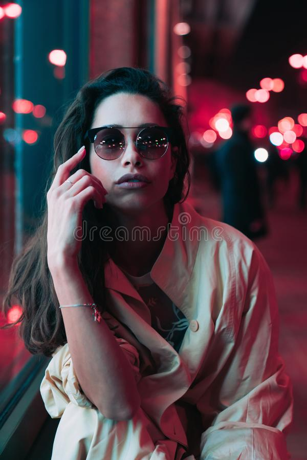 Noche en la ciudad, mujer hermosa entre luces rojas foto de archivo libre de regalías