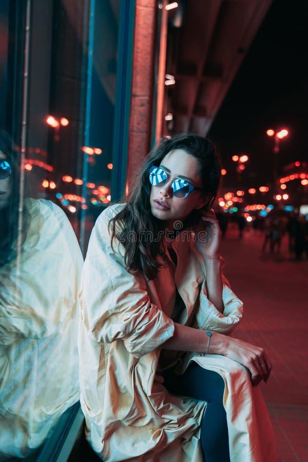 Noche en la ciudad, mujer hermosa entre luces rojas foto de archivo