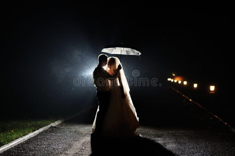 Noche feliz de novia y del novio con el paraguas foto de archivo libre de regalías