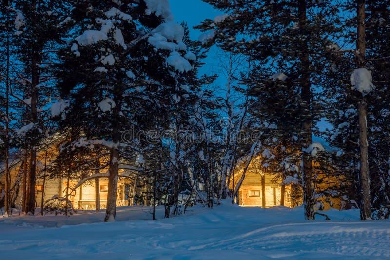 Noche fría del invierno, pequeñas casas de madera con la luz caliente foto de archivo