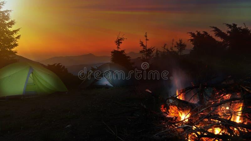 Noche que acampa en monta?as Hoguera brillante que quema cerca de la tienda dos Salida del sol imagen de archivo