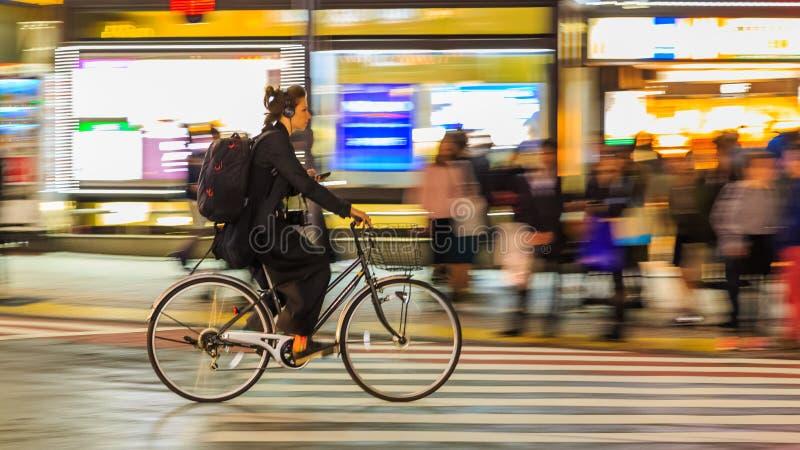 Noche que critica fotografía de la bicicleta no identificada del montar a caballo de la mujer en el cuadrado de Shibuya El que es imágenes de archivo libres de regalías