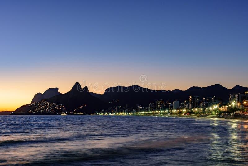 Noche que llega la piedra de Arpoador, playa de Ipanema en Rio de Ja imágenes de archivo libres de regalías