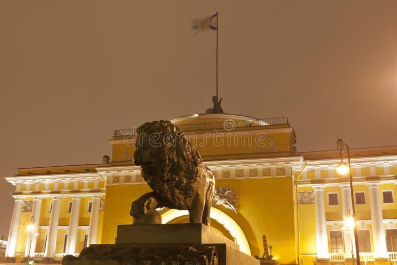 Noche St Petersburg, Rusia Escultura del león en un pabellón oriental del fondo del Ministerio de marina fotos de archivo