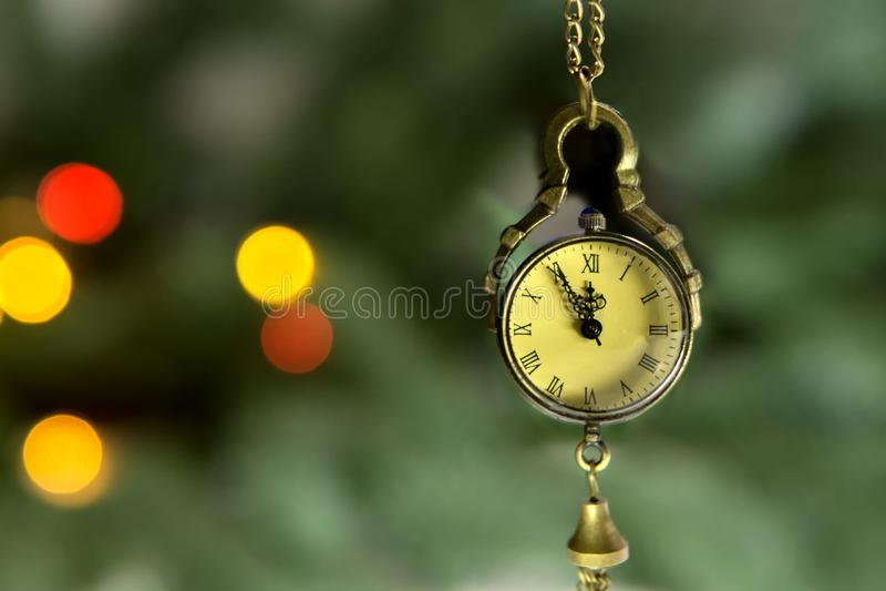 Nochevieja, el reloj - el medallón muestra 23 55 Pronto un nuevo rato en el fondo de un árbol de navidad verde imagen de archivo libre de regalías