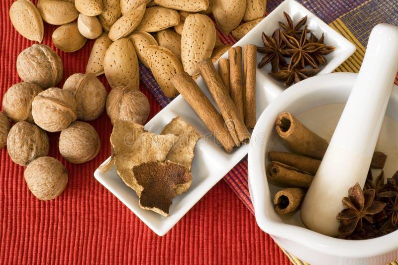 Noci e spezie grezze sulla tabella di cucina. fotografia stock libera da diritti
