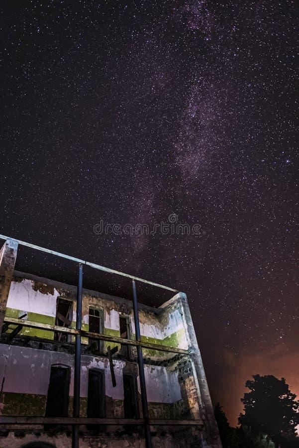 Nocne niebo i droga mleczna nad starym zaniechanym domem obraz royalty free