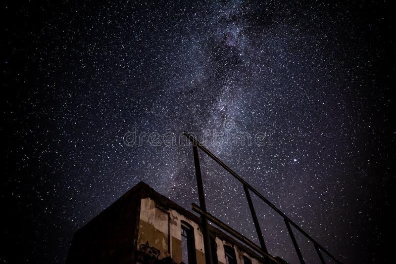 Nocne niebo i droga mleczna nad starym zaniechanym domem zdjęcie royalty free