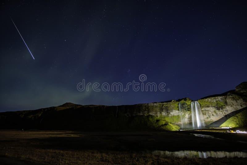 Nocne niebo nad Seljalandsfoss z opadającą gwiazdą obrazy royalty free
