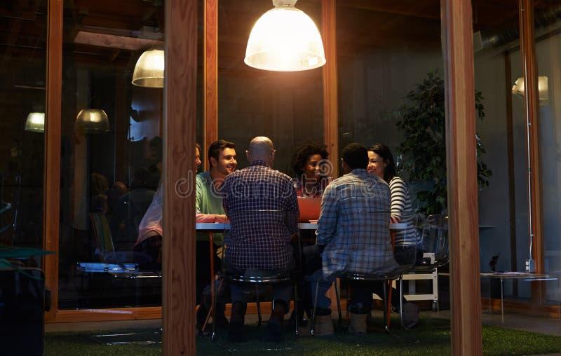 Nocny spotkanie Wokoło stołu W projekta biurze zdjęcia stock
