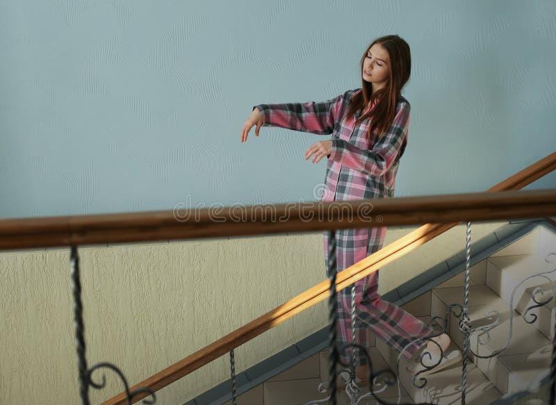 Noctambulist fêmea novo que anda abaixo das escadas imagem de stock