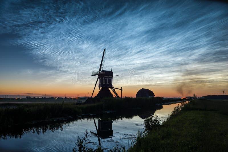 Noctilucent wolken over het Nederlandse landschap met windmolen langs een kanaal Een de brandritueel wordt van de midzomernacht g royalty-vrije stock afbeelding