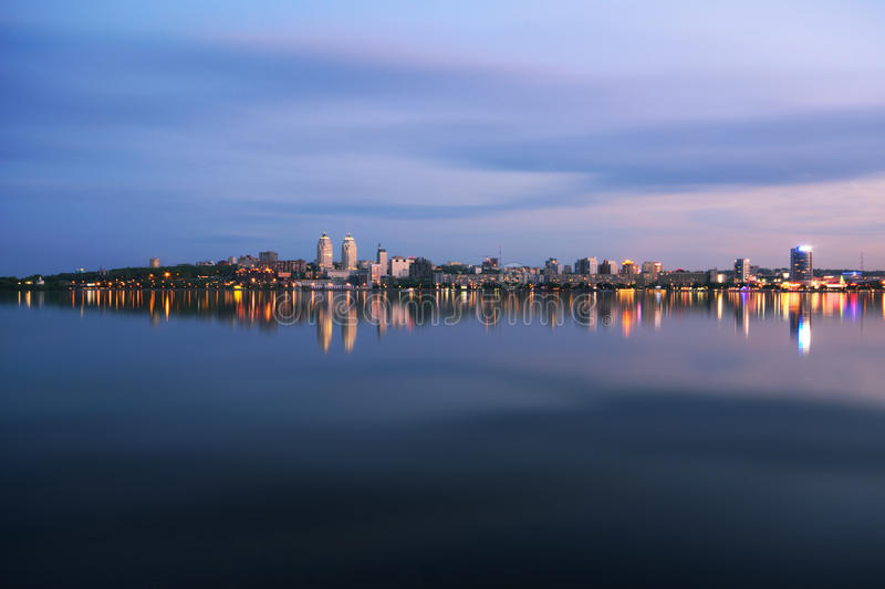Nocturnal pulse. Vew from the reflection of the waterfront at dusk Dnipropetrovsk stock image