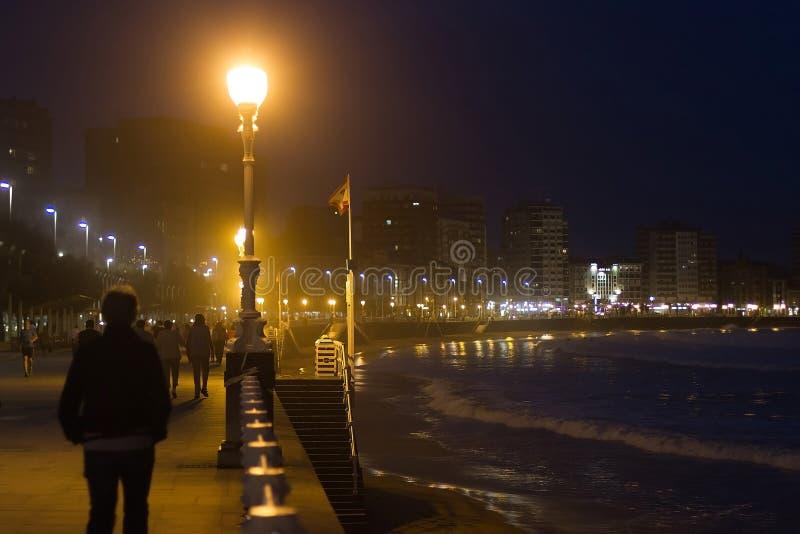 Nocturne av går och stranden av Gijon grensle arkivfoto
