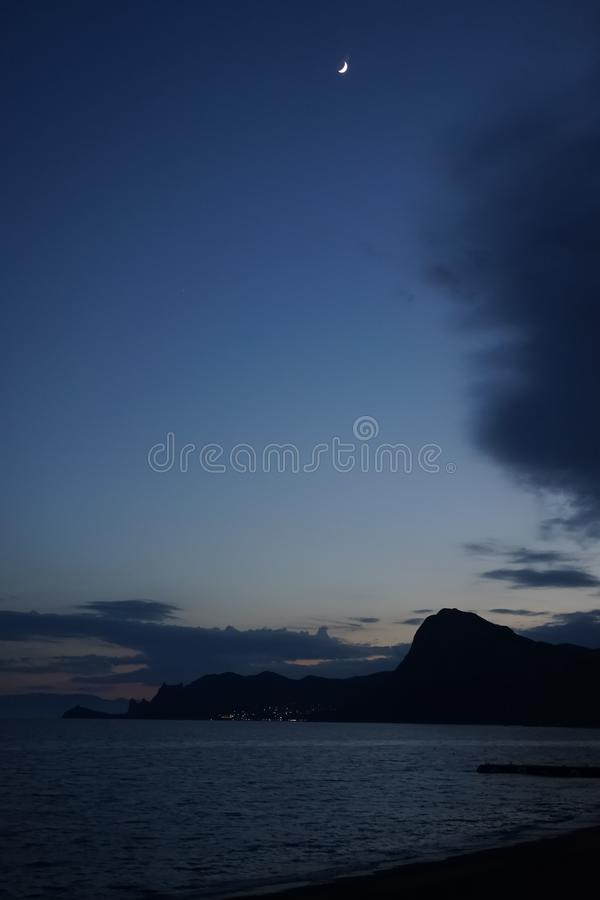 Nocy fotografia morze krajobraz z górami i księżyc w niebie obrazy royalty free