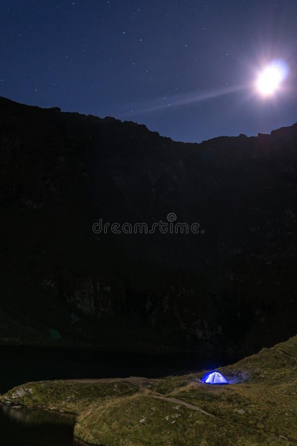 Nocy góry krajobraz z iluminującym błękitnym namiotem Halni szczyty i księżyc plenerowy przy Lacul Balea jeziorem, Transfagarasan obraz stock