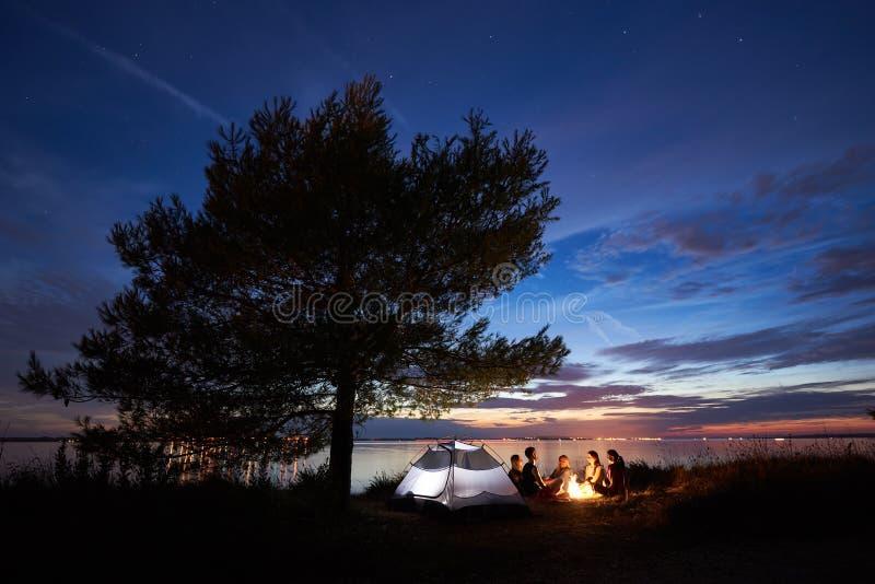 Nocy lata camping na brzeg Grupa m?odzi tury?ci woko?o ogniska blisko namiotu pod wiecz?r niebem fotografia stock