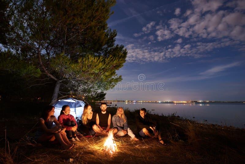 Nocy lata camping na brzeg Grupa m?odzi tury?ci woko?o ogniska blisko namiotu pod wiecz?r niebem obraz royalty free