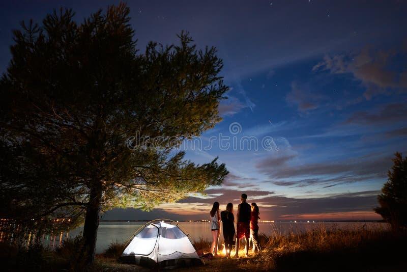 Nocy lata camping na brzeg Grupa m?odzi tury?ci woko?o ogniska blisko namiotu pod wiecz?r niebem zdjęcia stock