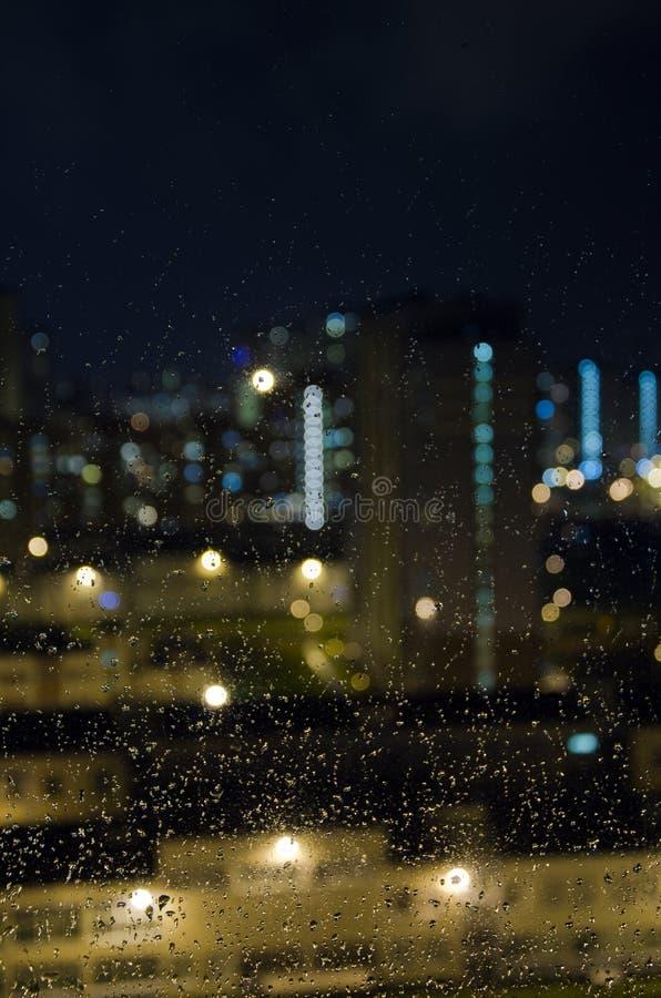 Nocy miasto w deszczu za nadokiennym szkłem zdjęcie stock