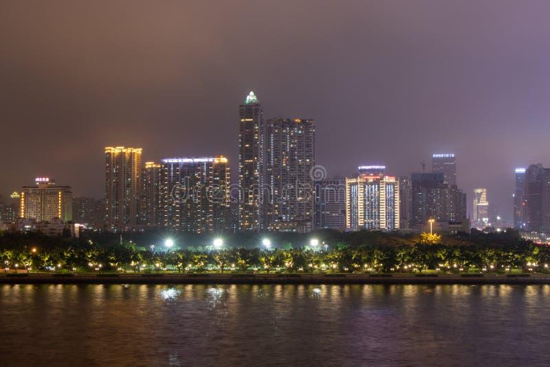 Nocy nowożytny miasto z drapacz chmur (Guangzhou) Most nad rzeką, miasto budynki jarzy się przy nocą fotografia stock