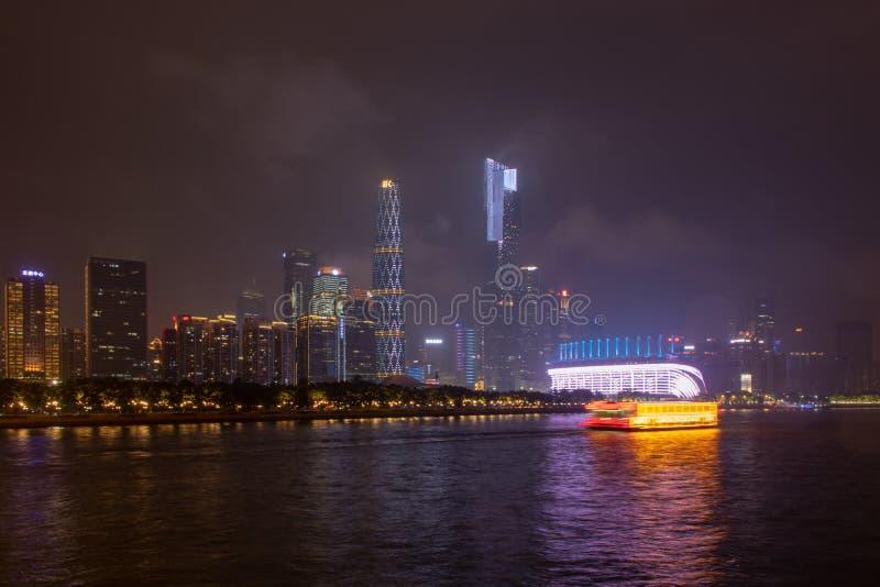 Nocy nowożytny miasto z drapacz chmur (Guangzhou Most nad rzeką, miasto budynki jarzy się przy nocą Quay z drzewami, światło poły obrazy stock