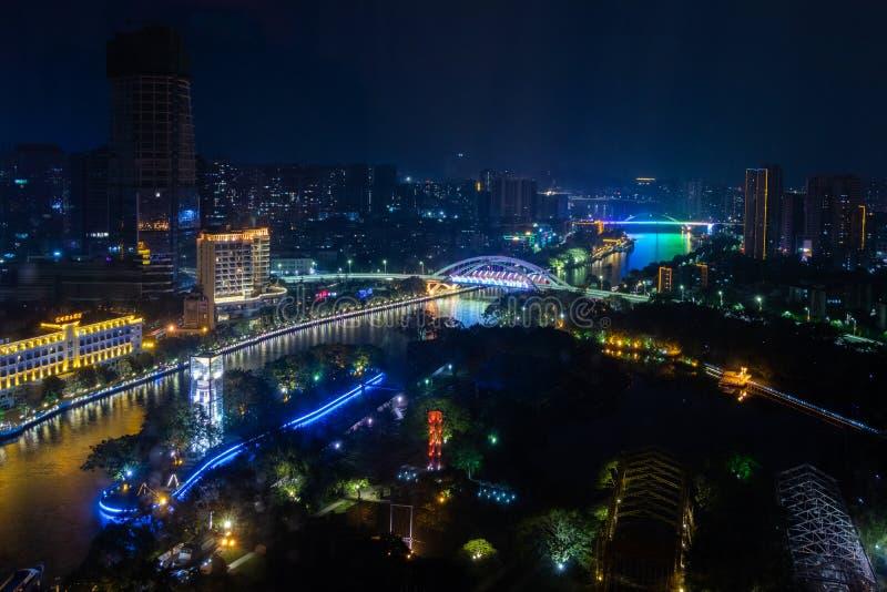 Nocy nowożytny miasto z drapacz chmur mostem nad rzeką, miasto budynki jarzy się przy nocą (Guangzhou) Quay z drzewami, światło p obraz stock