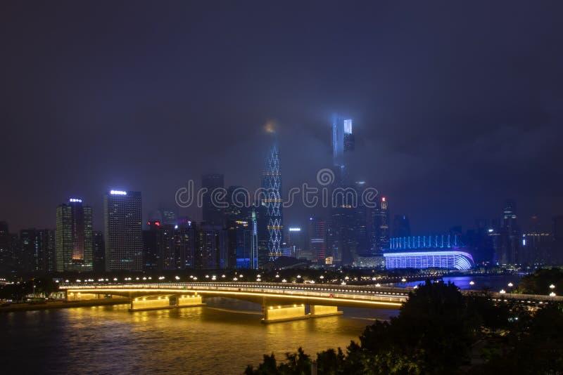 Nocy nowożytny miasto z drapaczami chmur Most nad rzeką, miasto budynki jarzy się przy nocą Niebo w chmurach chuje budynek obrazy stock