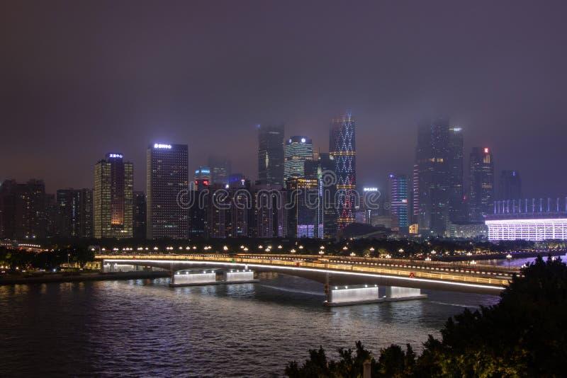 Nocy nowożytny miasto z drapaczami chmur Most nad rzeką, miasto budynki jarzy się przy nocą Niebo w chmurach chuje budynek obraz royalty free