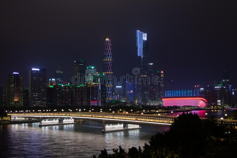 Nocy nowożytny miasto z drapaczami chmur Most nad rzeką, miasto budynki jarzy się przy nocą Niebo w chmurach chuje budynek fotografia stock