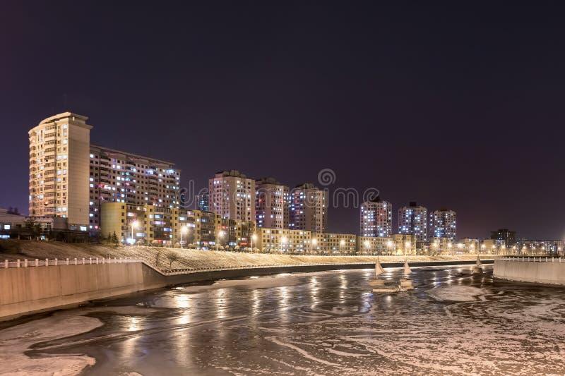 Nocy scena z budynku mieszkaniowego pobliskim marznącym kanałem, Changchun, Chiny fotografia stock