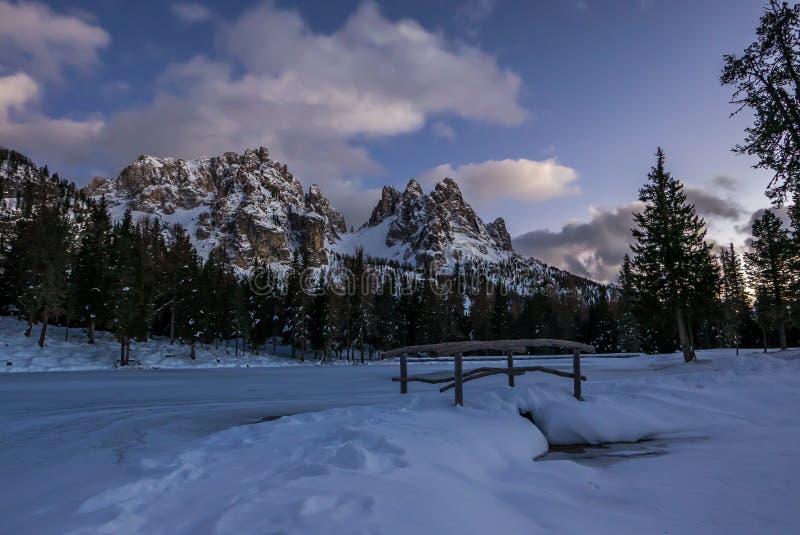 Nocy zimy wysokogórska sceneria z małym mostem na zamarzniętym jeziorze obraz stock