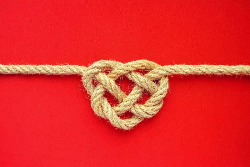 Nodo della corda di forma del cuore su fondo rosso Nodo del celtico della corda della iuta immagini stock