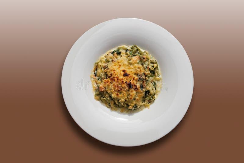 Noedelgratin met spinazie en gebraden zalm, close-up stock afbeeldingen