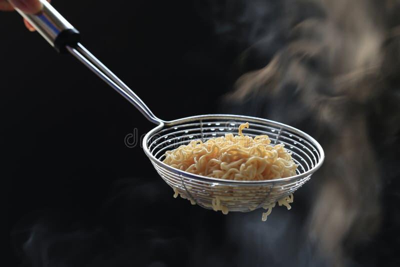 Noedels in mand met rook die op donkere achtergrond, zeer riskante de niermislukking van het Natriumdieet, Gezond het eten concep stock fotografie