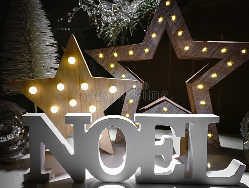 Noel词由木信件做成在背景阐明了机智 免版税库存照片