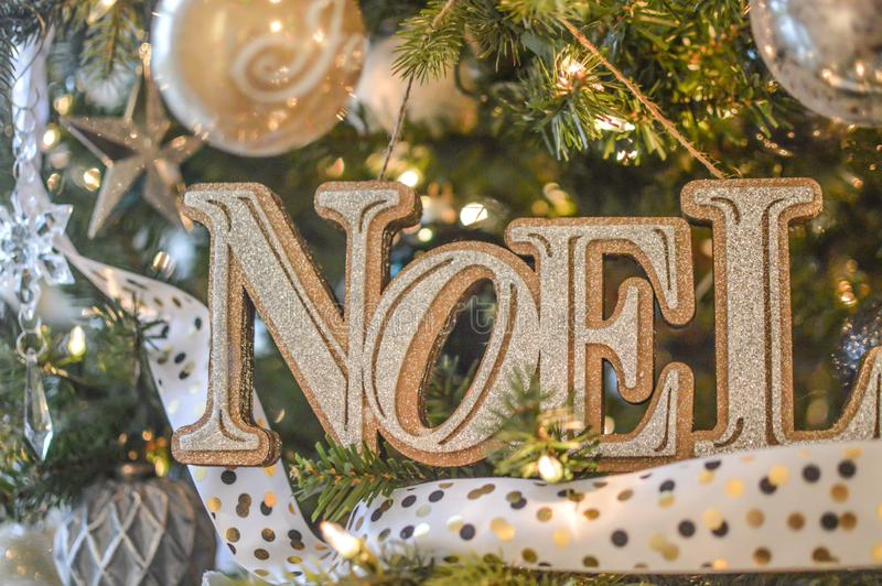 Noel - Gold Christmas Tree Ornament. A Noel gold and silver Christmas tree ornament with white bokeh ribbon and star and ball ornaments stock photos