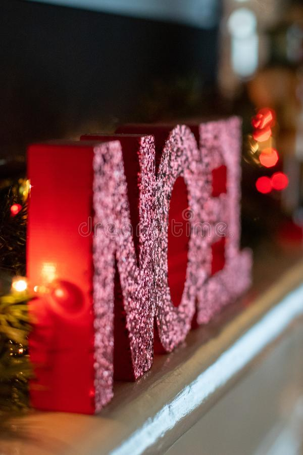 Noel sign in block letters on a mantel. Surrounded by Christmas lights and pine branches royalty free stock photo