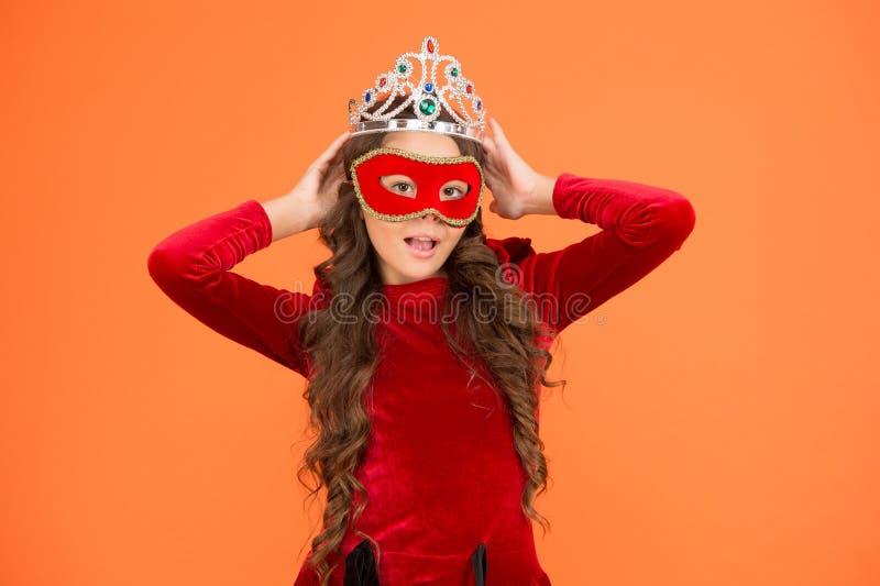 Noem me maar een grote baas. Grote baas, oranje achtergrond Kleine meisjesbaas draagt kroon en masker Ambitieus kind Prom stock foto