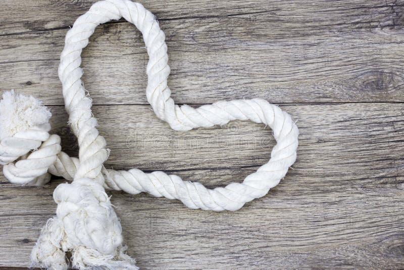 Noeud en forme de coeur sur une corde sur le fond en bois photos stock
