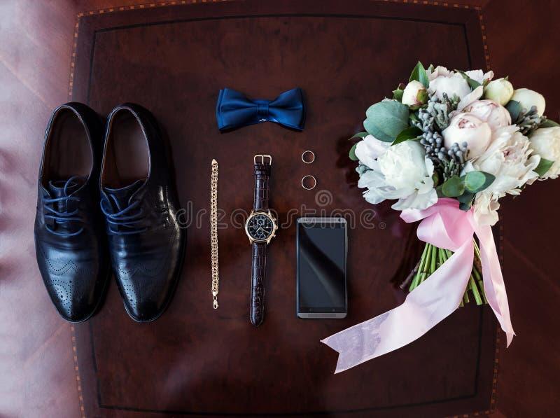 Noeud papillon, chaussures, anneaux de mariage, téléphone, horloge, bouquet du ` s de jeune mariée, photos stock