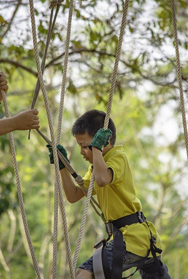Noeuds de gar?on d'ASEAN la corde et sourire heureusement dans l'arbre trouble de fond d'aventure de camp photographie stock