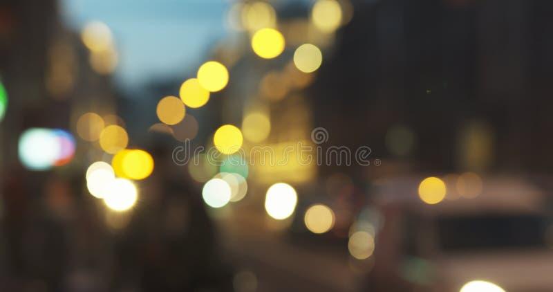 Nog onduidelijk beeldachtergrond van nachtstad met het bewegen van auto's en het lopen van mensen stock afbeeldingen
