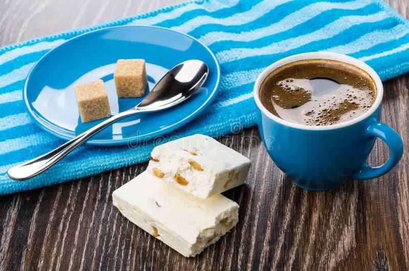 Noga, gestreept servet, suikerkubussen, lepel in schotel, koffie royalty-vrije stock afbeeldingen